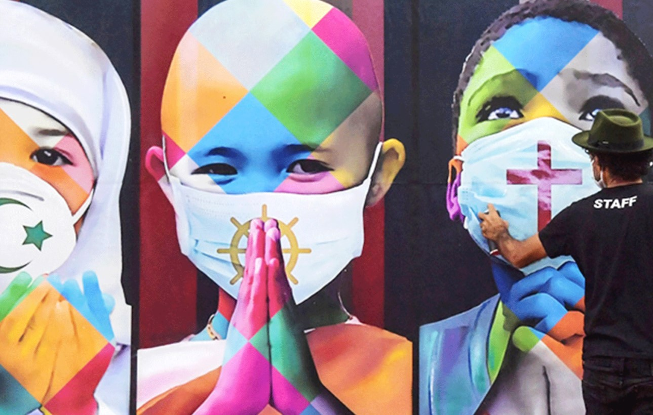 You are currently viewing Brazilian artist Eduardo Kobra paints a mural called 'Coexistence' amid the coronavirus pandemic